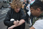 A young man uses a marker to write down the number of the National Lawyers Guild Hotline. The Guild provides lawyers and jail support to anyone arrested during these demonstrations. When asked the NLG also provides trained {quote}Legal Observers{quote} to monitor police and civil rights abuses during large gatherings, planned actions, and demonstrations such as took place on September 17th.