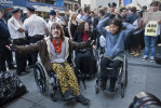 A group of wheelchair bound demonstrators rallya growing crowd forming around them after they were detained by police.