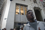 Office workers peer down from a second story window to watch OWS supporters passing by on the street below.