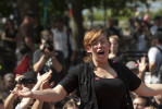 Pink confetti flutters down in front of a young woman as she addresses the Action Spokescouncil held by OWS supporters in Battery Park on September 17th 2012 the first anniversary of the Occupy Wall Street movement.