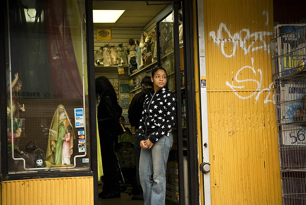 A young girl looks out onto Broadway from the doorway of Botanica Santa Ana in Washington Heights. Behind her, patrons shop for amulets, folk medicines, statues and other religious materials.