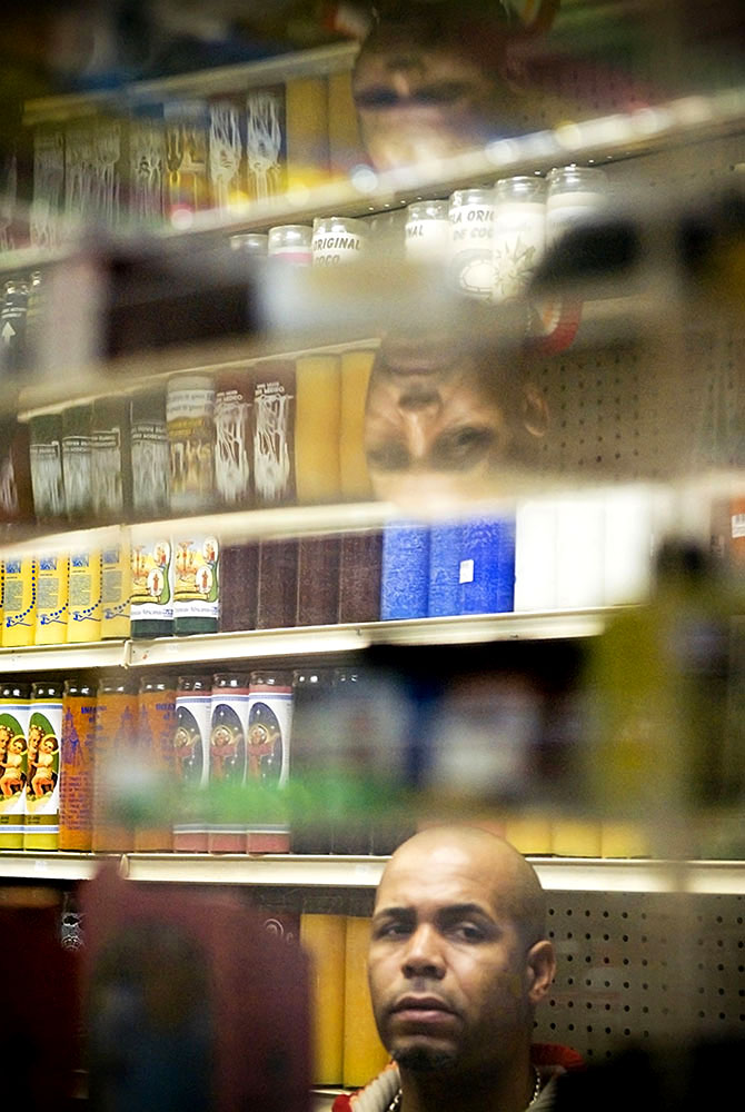 A patron at Santa Ana reflected in the lucite counter shelving. Behind him are rows of candles for sale.