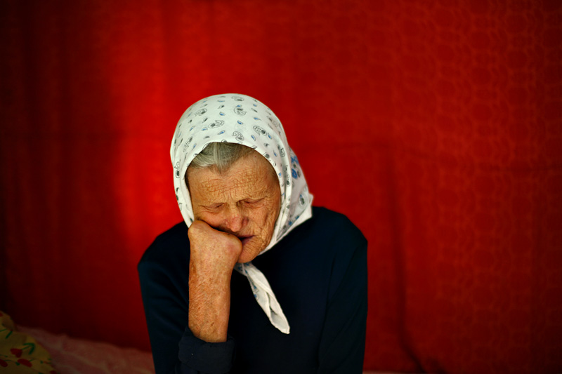 Ioana Miscov, 79 years old, rests in her house after eating her breakfast.  Ioana has been living here since she was 11 years old, when she was first brought by train, in an animal wagon.