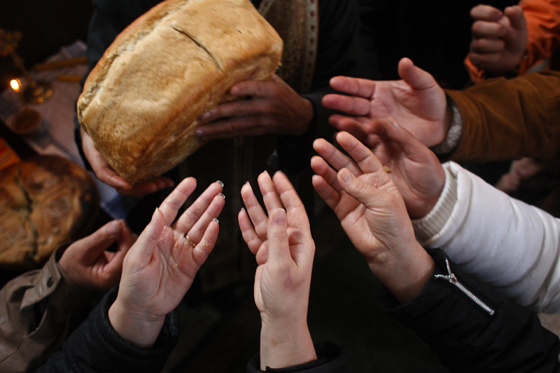 People reach for bread blessed by a priest during a religious ceremony in the village of Porodin.