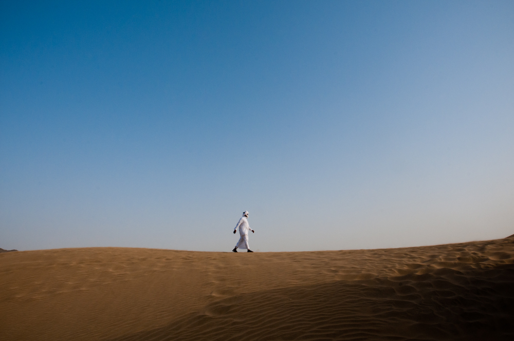 A lone bedouin walks across a sand dune in an area exactly between Makkah and Jeddah. Uncommon for the area, large sand dunes rise out of the rocky desert and dwarf everything around them.
