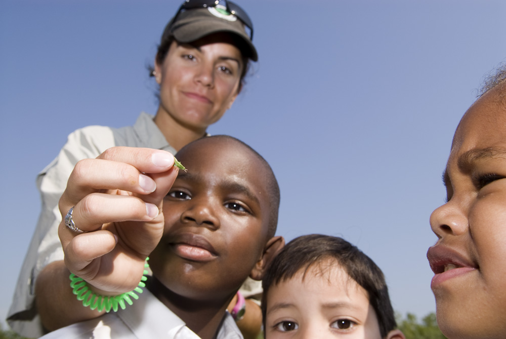 A Lake County Forest Preserve Educator holding an aphid for the elementary school children to observe during their field trip to the Greenbelt Forest Preserve