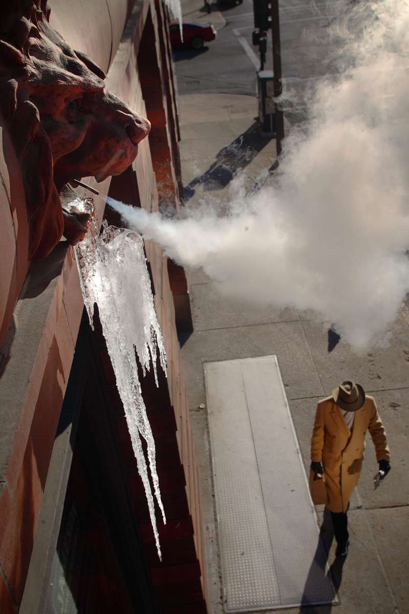 Terrance Bullock, of St. Louis, walks under the steam spouting from the lions head on the Bee Hat Lofts along N. 11th Street on Thursday.  Freezing temperatures with day time highs in the teens are expected to continue for the next three days.  The steam was added to the building as an ornamental detail when it was renovated into lofts from 2005-2006.