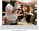 A looter with a gun in his waistband steals items from a QuikTrip in Ferguson after riots broke out after a candlelight vigil for Michael Brown on Saturday, Aug. 10, 2014. Hours earlier, hundreds of people had peacefully gathered for a vigil on the spot where Brown, an unarmed black 18-year-old, was shot and killed by Darren Wilson, a white Ferguson police officer. Police were also present at the vigil, but as dusk gave way to night, the crowd's frustration turned to anger. Rocks and bottles were thrown at officers and police responded with dogs, riot gear and an armored truck. A short time after this photo was shot the store was set on fire.Photo by David Carson, dcarson@post-dispatch.com