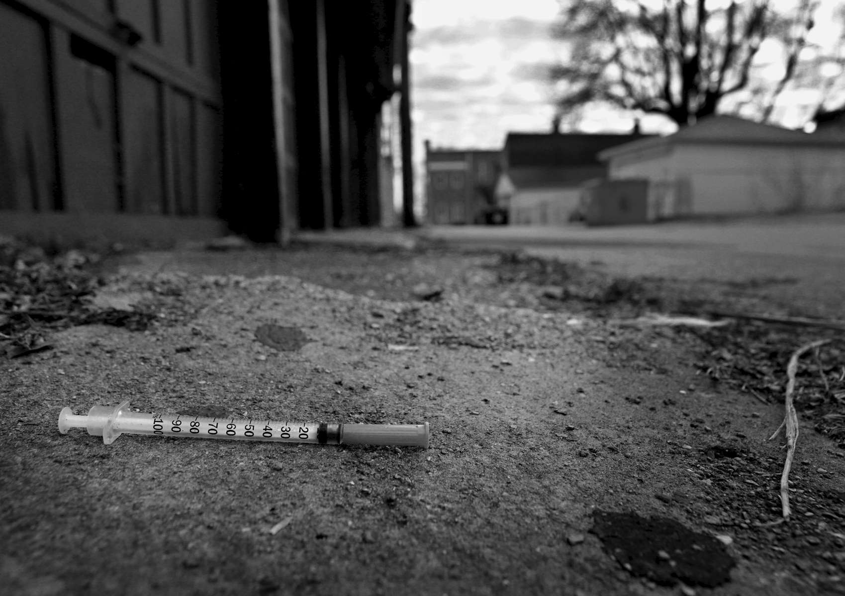 A discarded syringe is left in an alley behind a dilapidated apartment building on South Grand Boulevard in St. Louis on Thursday, Feb. 9, 2017. A year earlier, heroin user Eric Bearden, 28, died of a heroin overdose inside the apartment building. The alley is still known for it's drug use.