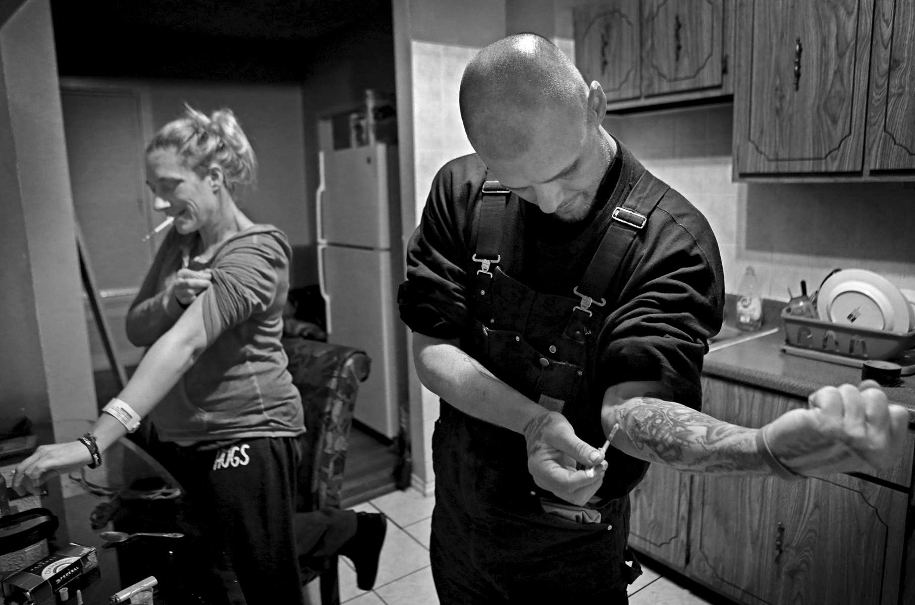 Ashley Johnston and Richard Skinner shoot heroin in the kitchen of Johnston's home in St. Louis on Monday, Feb. 6, 2017. Both have used heroin off and on for years. Johnston, who is six months pregnant with her fourth child, is trying to kick her habit with methadone, but recently missed a few methadone doses because of car problems. Skinner says he uses his stints in jail to get clean. Johnston and Skinner have one child together. Johnston and Skinner's child is cared for Johnston's mother who also cares for Johnston's other two children. In 2016 273 city residents last year, more than double the previous year, died of fatal opioid overdoses. Heroin is being cut with fentanyl to increase the high but the fentanyl is so powerful it leading to a sharp increase in deaths from overdoses.