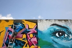 A graffiti artist from Kansas City works on putting the finishing touches on his work on the flood wall south of the Arch on Wharf Street in St. Louis. About 140 graffiti artist from around the country came to St. Louis to paint the flood wall.