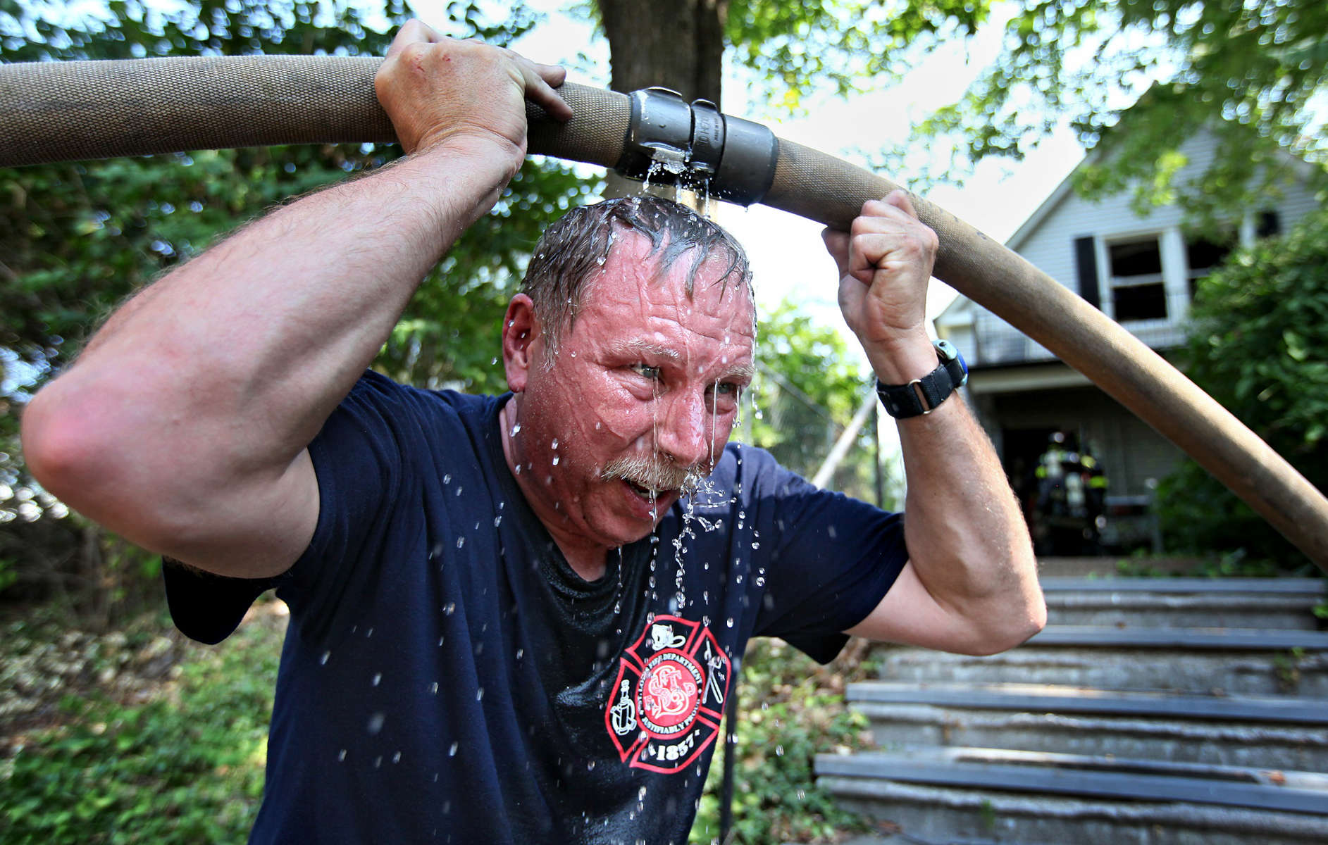 St. Louis fire fighter Ken Walters, with Truck 6, cools off with some water leaking from a fire hose after he helped put out a house fire in the 2000 block of McCausland Avenue in St. Louis on Monday, Sept. 9, 2013.  {quote}It was really cooking in there{quote} said Walters who was one of the first fire fighters in house battling the flames.  All the residents of the home escape safely and one was hurt in the one alarm fire.  Additional help from Maplewood and Richmond Heights fire departments was called to the scene as precaution against Monday's hot weather.Photo By David Carson, dcarson@post-dispatch.com