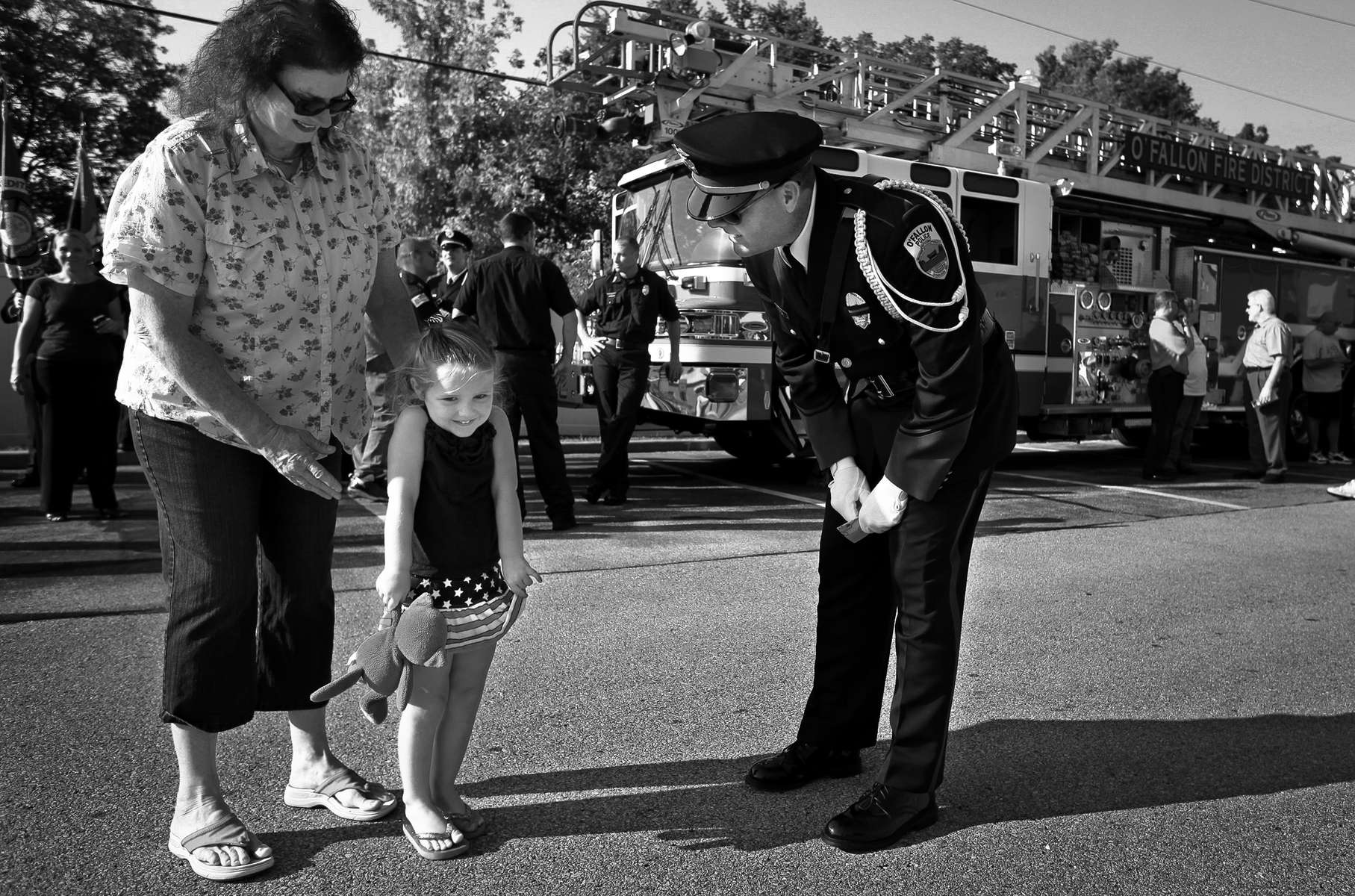 Jeanne Tallman escorts her granddaughter Whitney Weeks, 3, as she hands a coloring she did to O'Fallon police officer Mike Plum after a ceremony honoring first responders in O'Fallon, Mo. on Wednesday, Sept. 11, 2013.  {quote}She wanted him (Plum) to know she was thinking about them{quote} said Tallman who said the coloring paid tribute to the fire fighters and police officers who gave their lives on September 11.  The City of O'Fallon, Mo. hosted a Patriot Day Ceremony, a Tribute to First Responders by a piece of the twisted steel from the World Trade Center at the Municipal Centre.Photo By David Carson, dcarson@post-dispatch.com