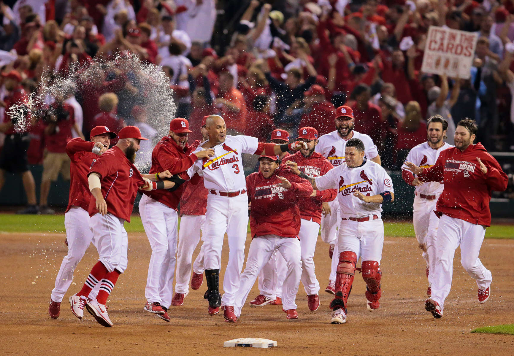 Carlos Beltran is mobbed by his teammates after connecting on the game inning hit in the 13th inning of Game 1 of the National League Championship Series between the St. Louis Cardinals and the Los Angels Dodgers on Friday, Oct. 11, 2013, at Busch Stadium in St. Louis.
