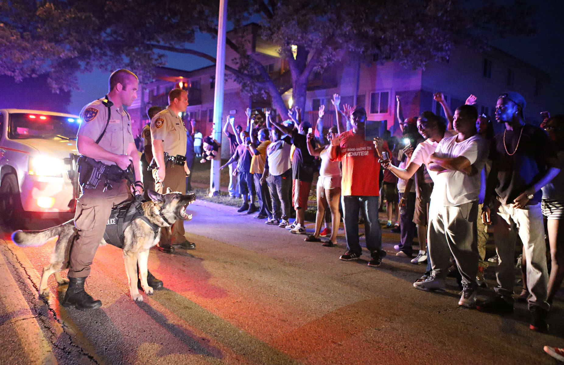 Police officers confront a crowd they're trying to break up a on Canfield Dr. in Ferguson, Mo. on Saturday, Aug. 9, 2014. Earlier in the day police had shot and killed Michael Brown, an unarmed18 year-old man, and community members turned out large numbers at the scene to express their outrage.