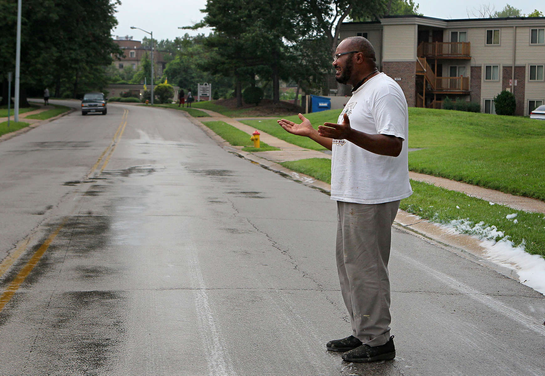 The pavement still wet from being hosed down to wash blood off the road, Pastor Charles Ewing grieves and prays near the spot his nephew Michael Brown Jr. was shot and killed by Ferguson police officer Darren Wilson in Ferguson, Mo. on Saturday, Aug. 9, 2014.  Ewing was the first person to stand on the spot after the crime scene tape came down and police left the area.
