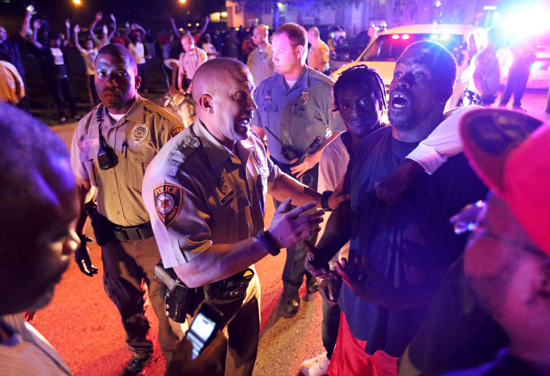 Police officers speak to a man as they try to calm down and break up a crowd on Canfield Dr. in Ferguson on Saturday, Aug. 9, 2014. Earlier in the day police had shot and killed Michael Brown, an unarmed18 year-old man, and community members turned out large numbers to express their outrage.  Police officers eventually withdrew from the apartment complex.