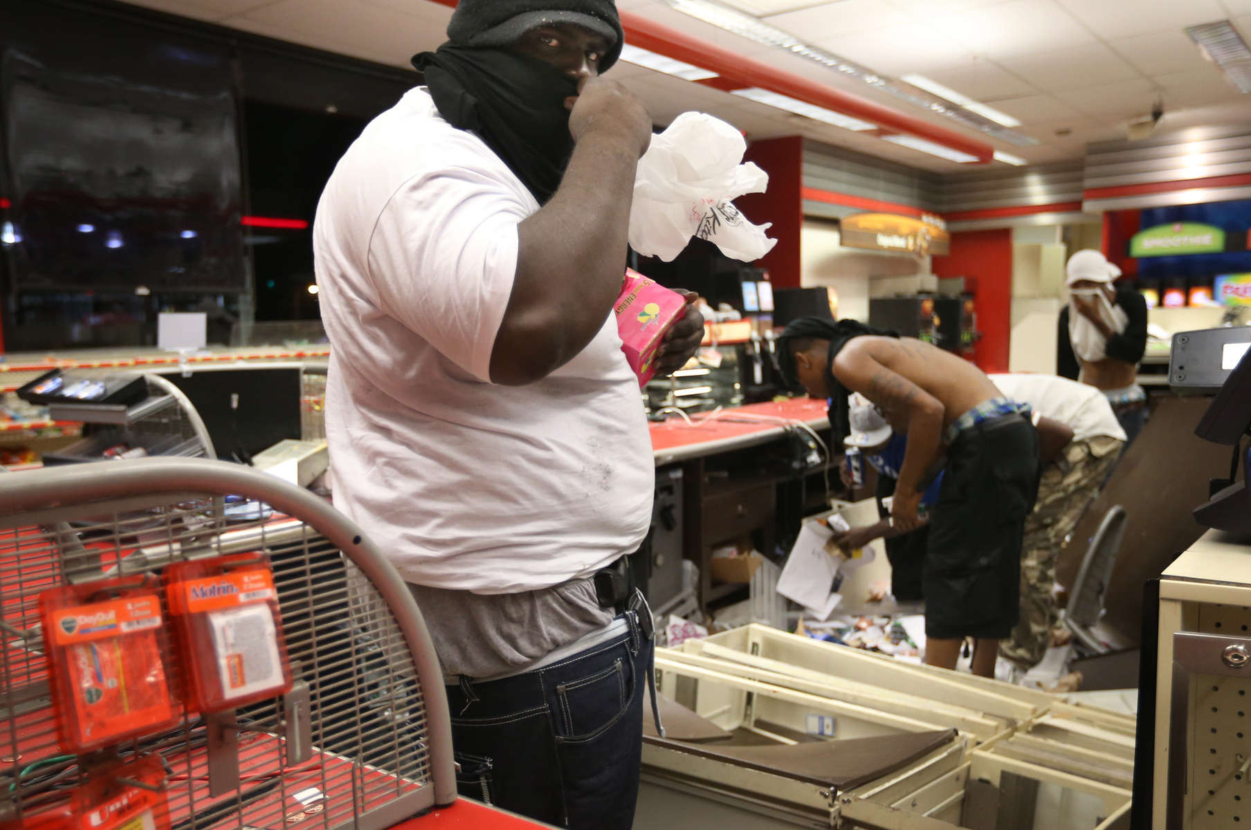 A looter armed with a gun takes items inside the QuikTrip in 9400 block of W. Florissant Avenue in Ferguson, Mo. on Sunday, Aug. 10, 2014.  Rioters set fire to the store about an hour later.