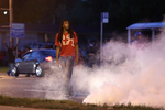 A man stare defiantly at police was he walks through a cloud of tear police deployed to dispersed a crowd at the corner of Lang Drive and W. Florissant Avenue on in Ferguson, Mo. Monday Aug. 11, 2014.