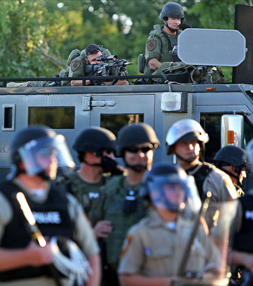 A police sharp shooter keeps an eye on protesters along W. Florissant Avenue near the QuikTrip that was burned down a few days earlier in Ferguson, Mo. on Tuesday, Aug. 12, 2014.