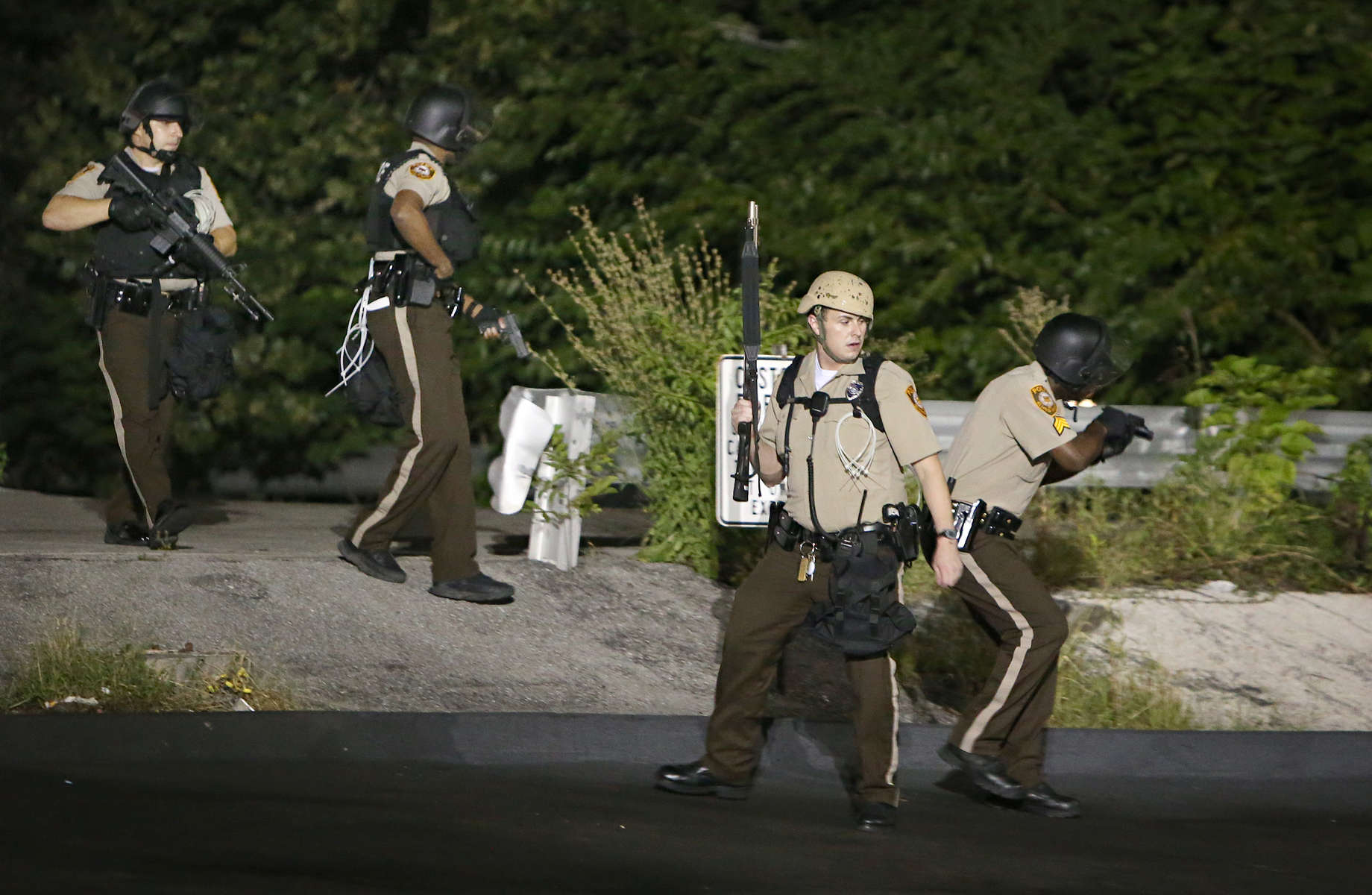 St. Louis County police officers keep an eye out for two armed men as they search the woods for gunmen along W. Florissant Avenue in Ferguson, Mo. on Tuesday, Aug. 13, 2014. A short time earlier police shot and critically wounded a different armed man.