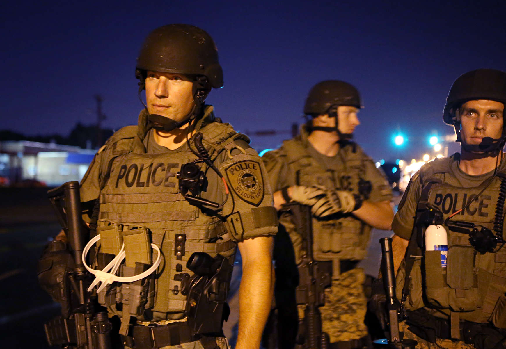 St. Louis County police officers watch as a group of protesters leave the area near the QuikTrip that was burned down a few days earlier in W. Florissant Avenue on Tuesday, Aug. 12, 2014.  Earlier in the night police showed restraint not shooting at a car that drove at high speed towards them stopping just thirty yards short of them.