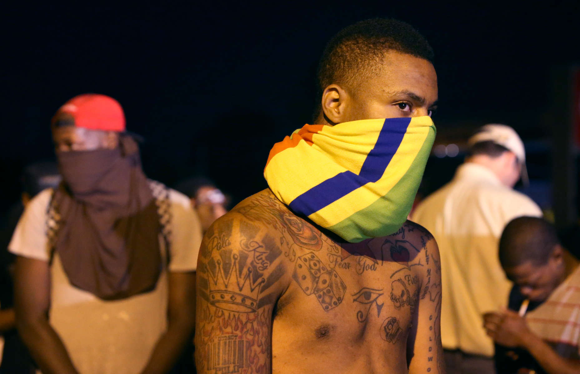 Protesters cover their face as they look toward the police blocking W. Florissant Avenue on Tuesday, Aug. 12, 2014 near the QuikTrip that was burned down a few days earlier in Ferguson.