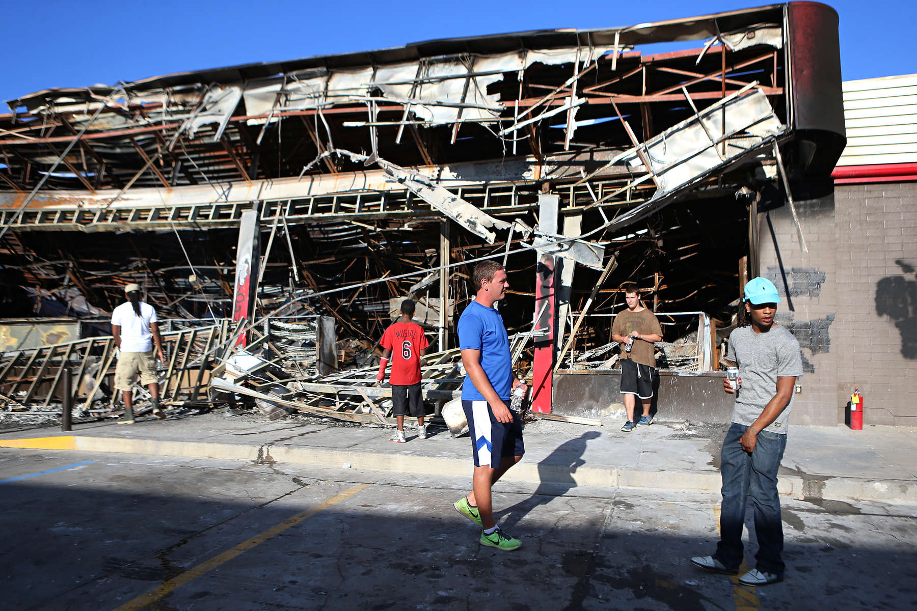 Brent Kirby (center), 23, from Florissant, and Del Foster (right), 20, from Ferguson, check out the burnt out QuikTrip in Ferguson, Mo. on Tuesday, Aug. 12, 2014.  The QuikTrip, that was burned down by looters two days earlier, become a focal point for clashes between police and protesters.
