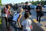 Women argue with police officers to let them pass and go home because they were afraid of being near the protest scene with their children if things turned violent along W. Florissant Avenue on Tuesday, Aug. 12, 2014.  The women were eventually allowed to pass, but not without a heated argument between them, the crowd and the police.Photo By David Carson, dcarson@post-dispatch.com
