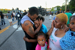 Terrell Williams El, comforts his daughter Sharell Williams, 9, as Temika Williams, 6, (bottom) stays close to her mom Shamika Williams, and sister Shanell Williams, 2, near a line of police in riot gear on West Florissant Ave. on Wednesday, Aug. 13, 2014.