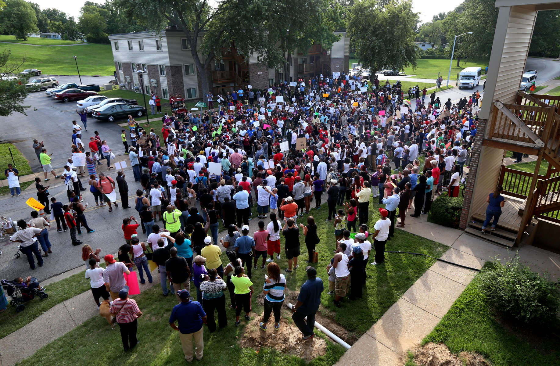 A crowd of protesters gather near the spot where Mike Brown was shot and killed by a police officer on Canfield Drive after they marched from Chamber Road on Thursday, Aug. 14, 2014.