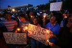 Keith Lovett (left), Melik Smith, Victoria Smith, Linda Smith and Antonio McDonald(right) hold candles during a gathering of people at the QuikTrip in Ferguson Thursday, Aug. 14, 2014.  Thursday marked the first peaceful night protests since Michael Brown was shot and killed by a police officer.
