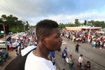 Jamel Easley, from the Walnut Park neighborhood in St. Louis city, takes in the scene from on top of a van parked at the corner of Canfield Drive and W Florissant Avenue on Sunday, Aug. 17, 2014.Photo By David Carson, dcarson@post-disptch.com