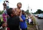 This is my Mike Brown{quote} says Jamile Thompson, of St. Louis City, as she holds her son Carter Ramey, 18 months, while calling out to cars passing the burnt out QuikTrip W. Florissant Avenue on Sunday, Aug. 17, 2014.Photo By David Carson, dcarson@post-disptch.com
