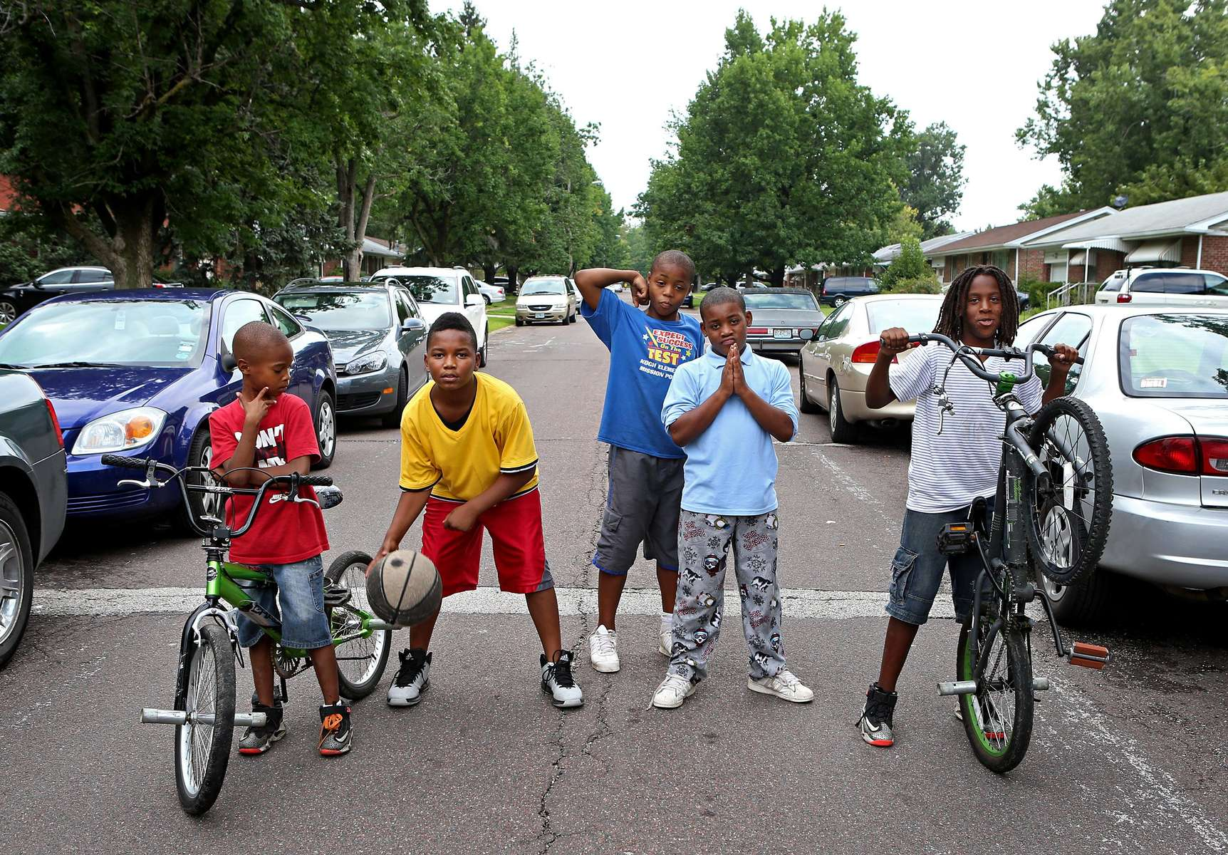 Friends Jaishyne Brister, 8, Jermell Sane, 11, Martez Bryant, 13, Armoni Whitaker, 10, and Chase Brister, 12, pose for a picture on Ward Drive in Ferguson a few blocks away from the honking and chants of protesters at the Mike Brown protests at the QuikTrip on Sunday, Aug. 17, 2014.