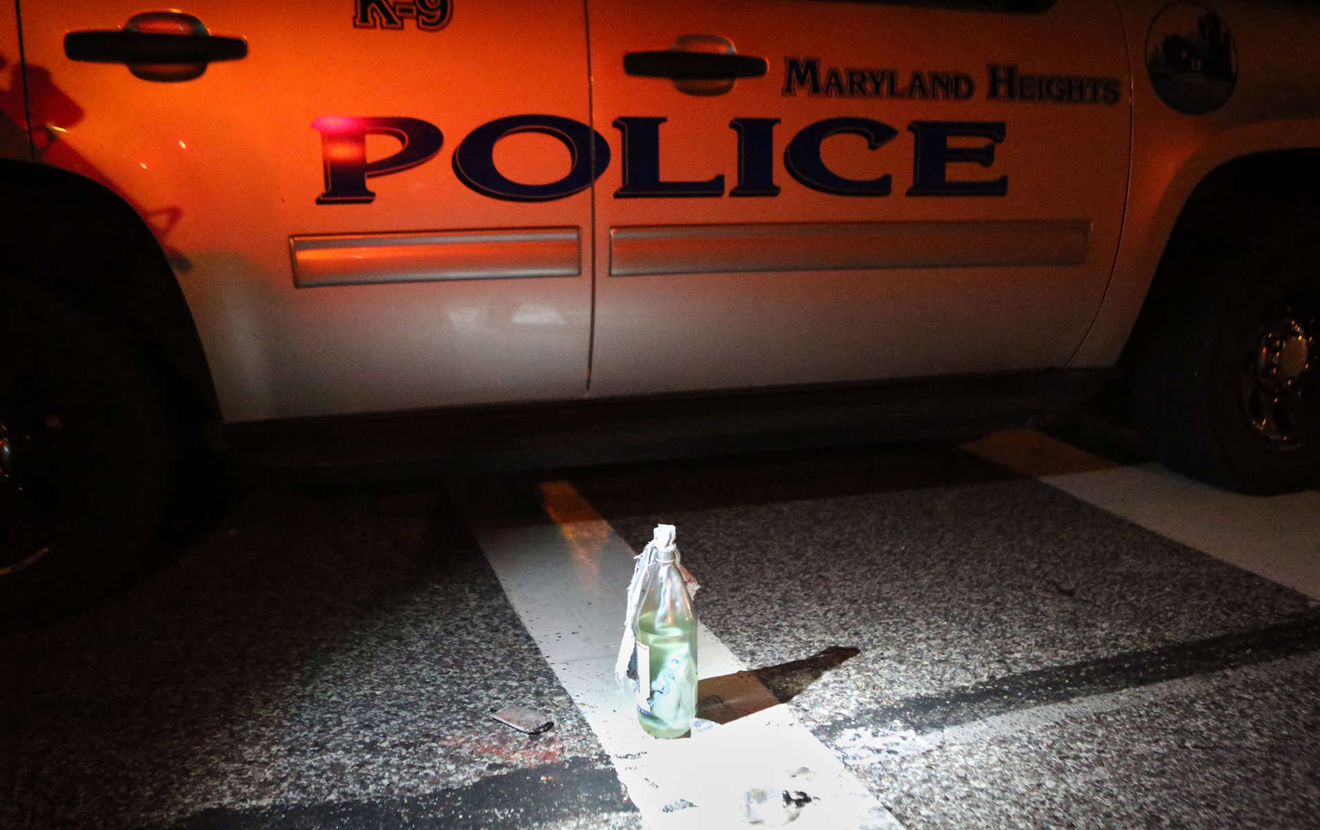A Molotov cocktail sits near a police car after it was removed from a truck carrying 12 people when it was stopped along W. Florissant Avenue near Canfield Drive in Ferguson on Tuesday, Aug. 19, 2014.  The police also found two loaded guns on the people in the truck.