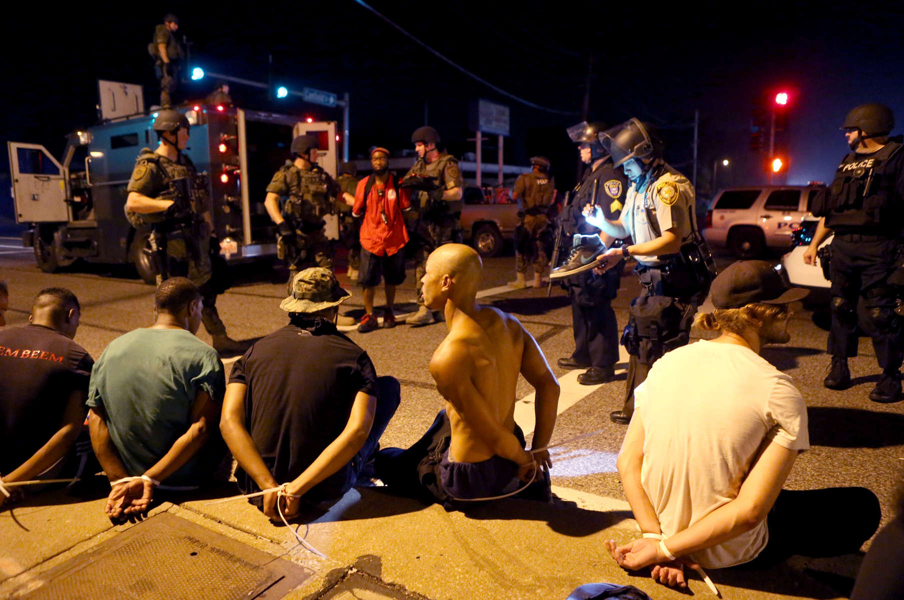 Members of the St. Louis County Police tactical team take a truck load of 12 people into custody after they stopped it driving along W. Florissant Road near Canfield Drive in Ferguson, Mo. on Tuesday, Aug. 19, 2014.  The police found two loaded guns on the people in the truck and removed a large Molotov cocktail from the truck.