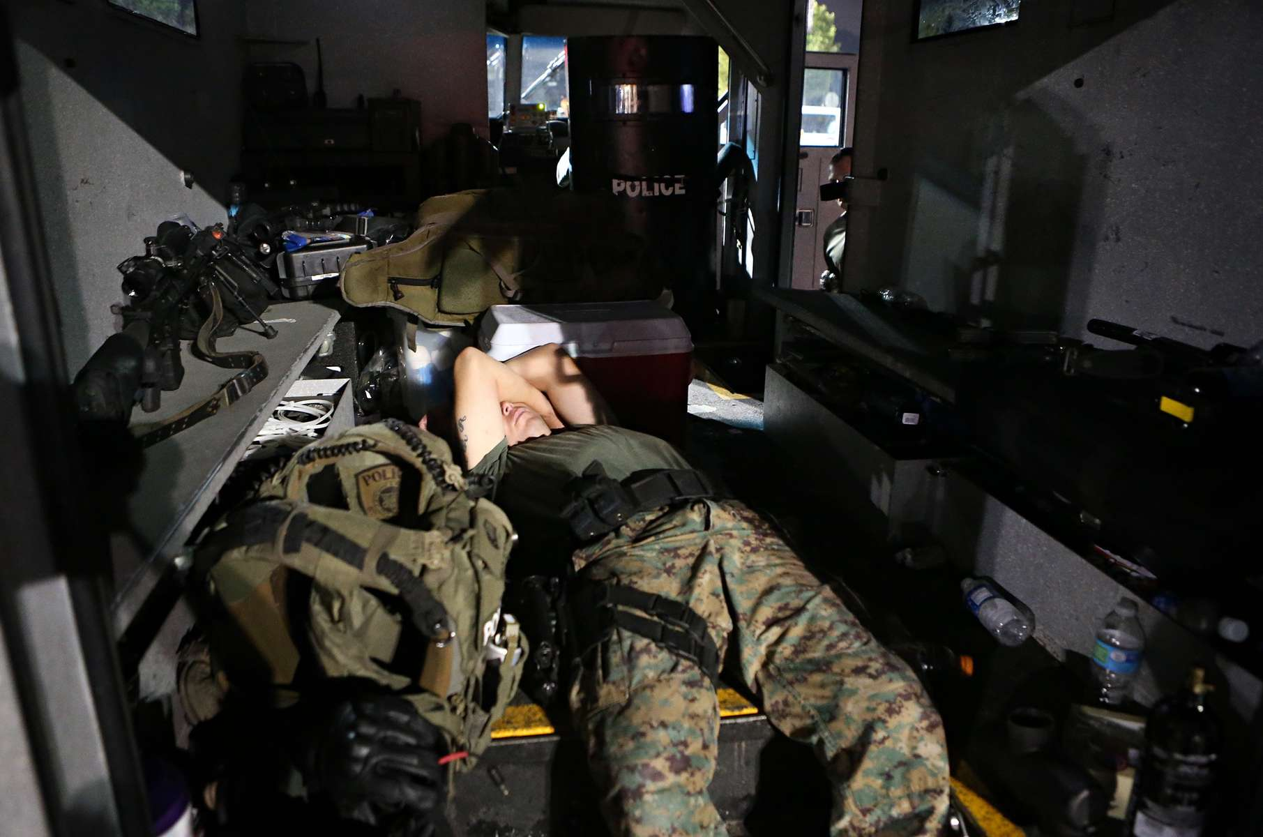 A member of the St. Louis County Police tactical team sleeps in the back of the team's armored truck after arriving back at the command post W. Florissant Avenue at about 2:49 A.M. on Tuesday, Aug. 19, 2014.