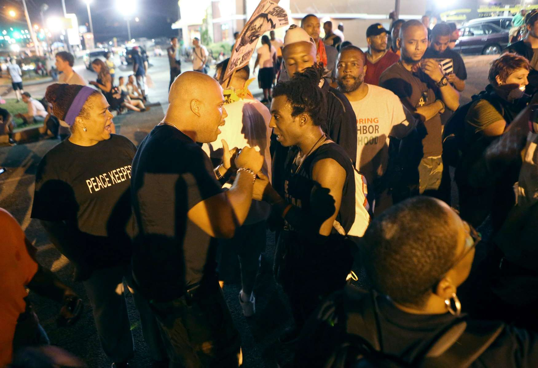 A Peace keeper (center left) and an man who was giving an impassioned speech advocating for a more confrontational protest argue near the McDonalds on W. Florissant Avenue in Ferguson on Sunday, Aug 24, 2014.   There was a debate in the crowd about what type of protest was going to be taking place with some people advocating a peaceful protest and others seeking a more confrontational approach.