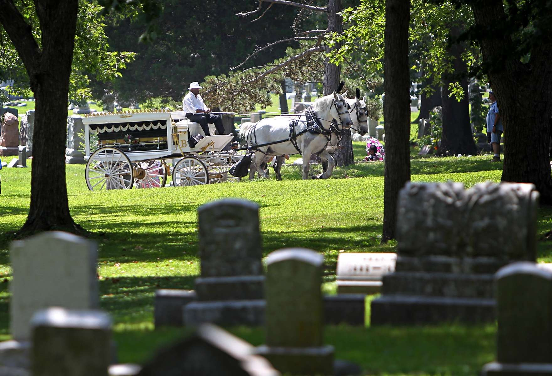 The casket of Michael Brown is taken by horse and carriage through St. Peters Cemetery to his gravesite in Normandy, Mo. on Monday, Aug. 25, 2014.