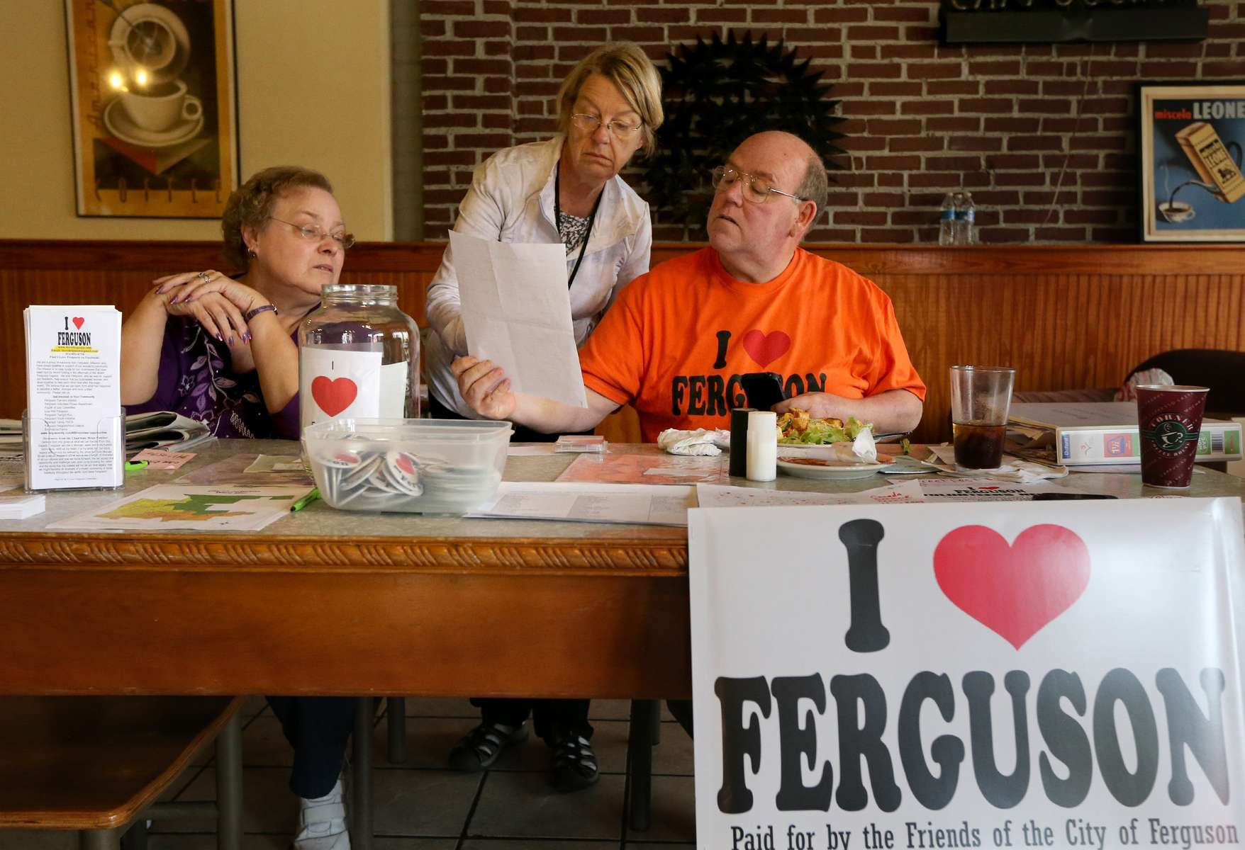 Elaine Wirt (left), Peggy Faul, and Brian Fletcher go over some paper work about the I ❤ FERGUSON committee at Corner Coffee House in Ferguson on Wednesday, Sept. 17, 2014. The committee that is selling the I ❤ FERGUSON shirts, buttons and yard signs recently received a letter from a man claiming the shirts violate his trademark on I ❤ FERGUSON.Photo By David Carson, dcarson@post-dispatch.com