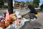 Tim Sneed kneels at Michael Brown's memorial that had burned earlier in the day as a new pile of stuffed animals and items began to appear at the spot on Canfield Drive on Tuesday, Sept. 23.  The fire started somewhere between 6:30 and 7 A.M