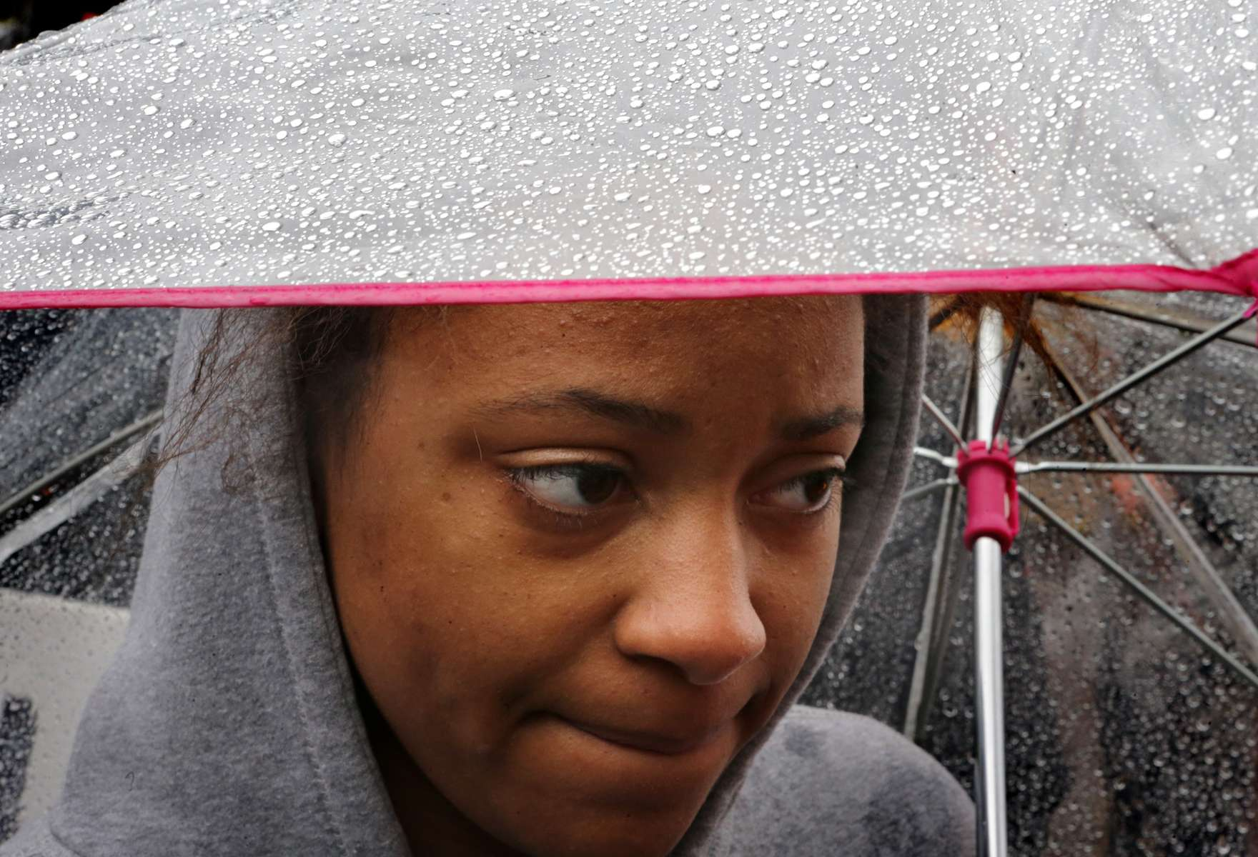 Lakeyra Stephens, 20, takes shelter from the rain under her umbrella after she marched with protesters around downtown Clayton during the first Ferguson October protests on Friday, Oct. 10, 2014.  About 400 people too part in the march and protest aimed at getting justice for Michael Brown and to get St. Louis County prosecuting attorney's Bob McCulloch to step aside and bring in a special prosecutor.  Stephens, a Webster University student from Texas, says she showed put show solidarity with the protesters.  She went on to say that she was surprised by the level of segregation she sees in St. Louis compared to Texas.