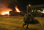 Police officers gather outside the Beauty Town building as it is engulfed in flames on Monday, Nov. 24, 2014. Photo By David Carson, dcarson@post-dispatch.com