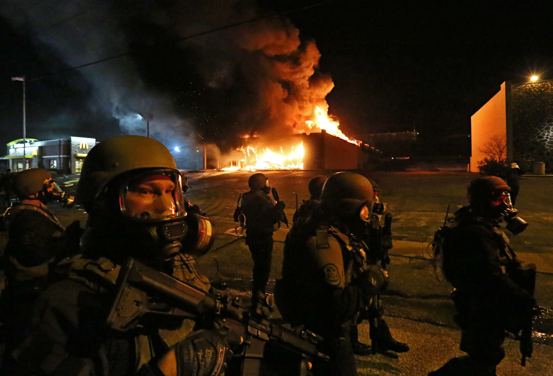 St. Louis County Police tactical team arrive on W. Florissant Avenue to disperse crowd as the Beauty Town store burns on Monday, Nov. 24, 2014. Photo By David Carson, dcarson@post-dispatch.com