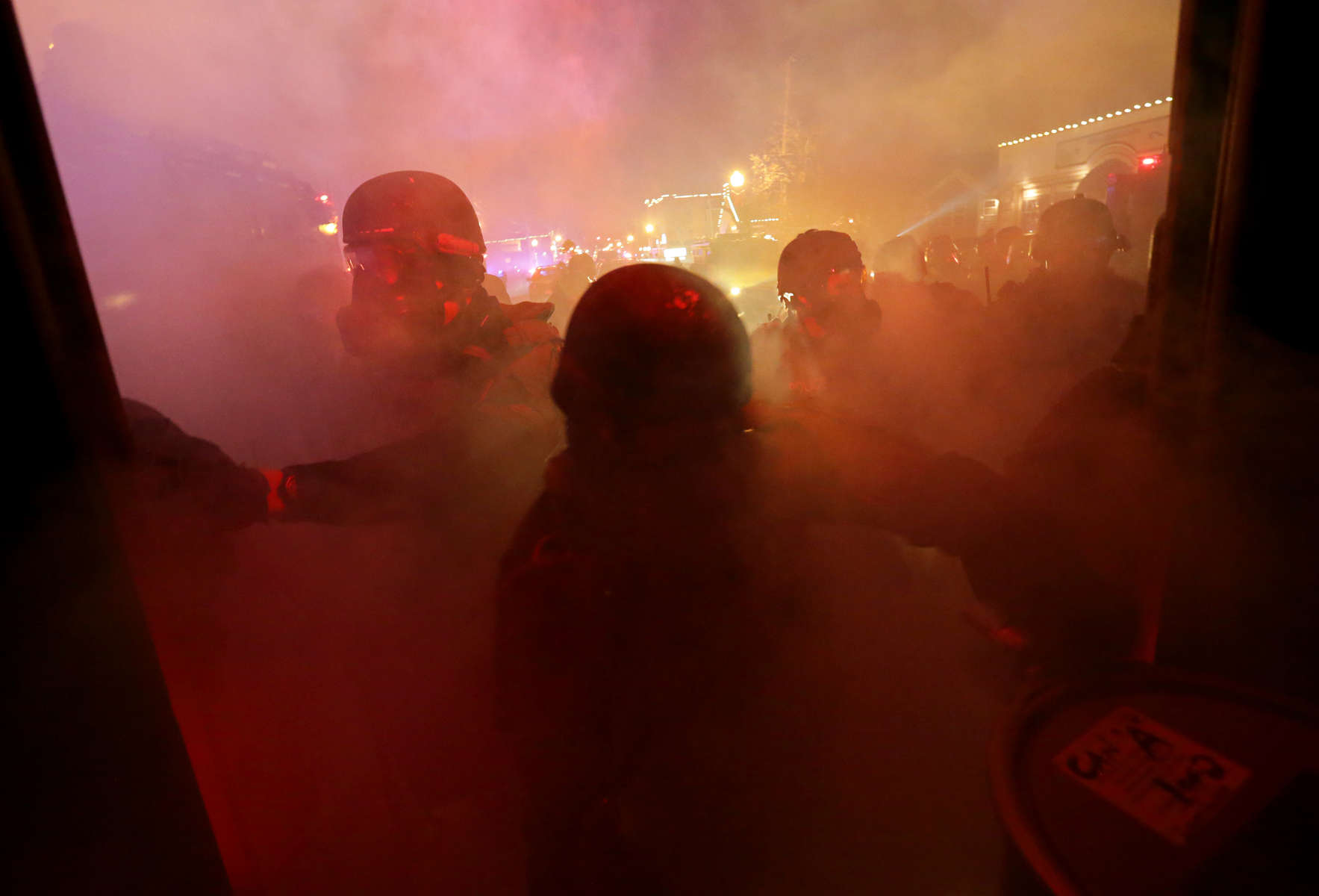 Members of the St. Louis County Police tactical team are engulfed in tear gas as they try to disperse a crowd near the Ferguson police station on S. Florissant Avenue in Ferguson on Monday, Nov. 24, 2014.Photo By David Carson, dcarson@post-dispatch.com