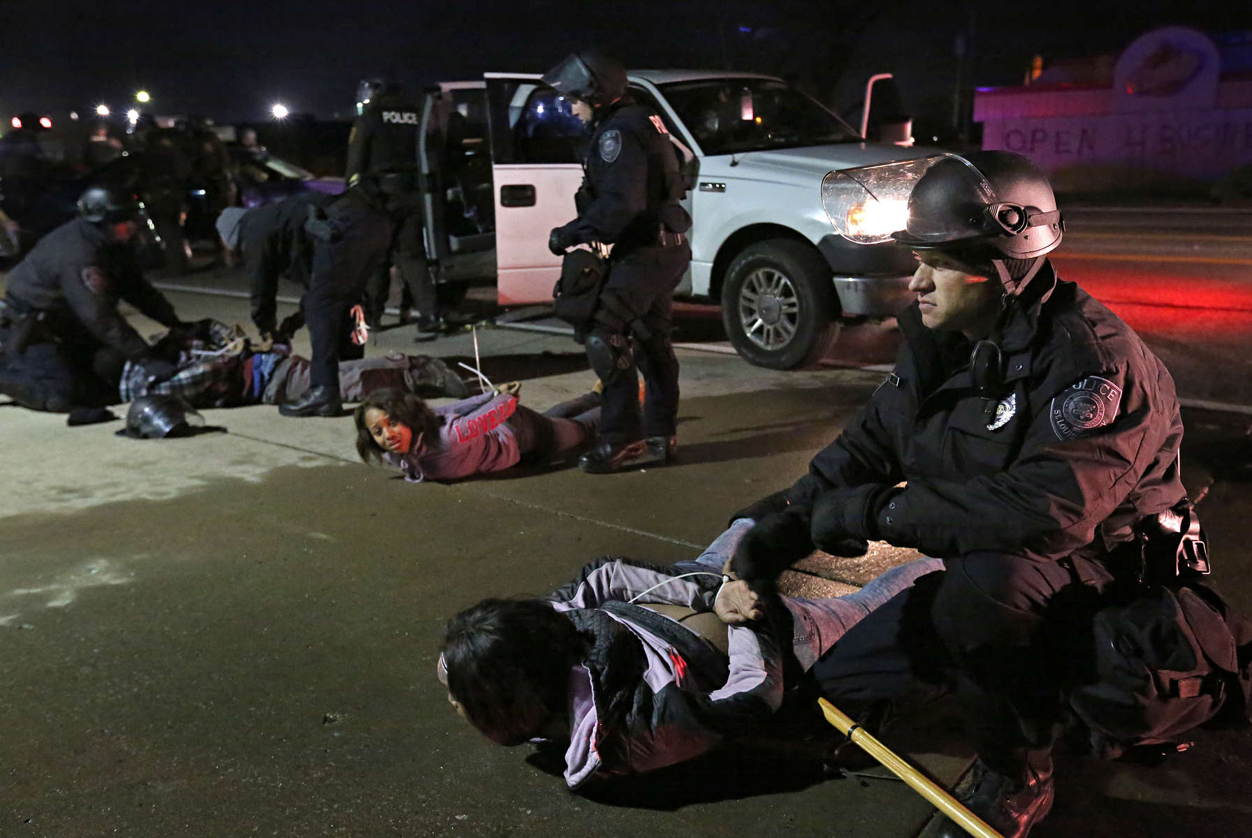 Police officers take a group of people into custody on New Halls Ferry Road on suspicion of looting in Ferguson on Tuesday, Nov. 25, 2014. Photo By David Carson, dcarson@post-dispatch.com