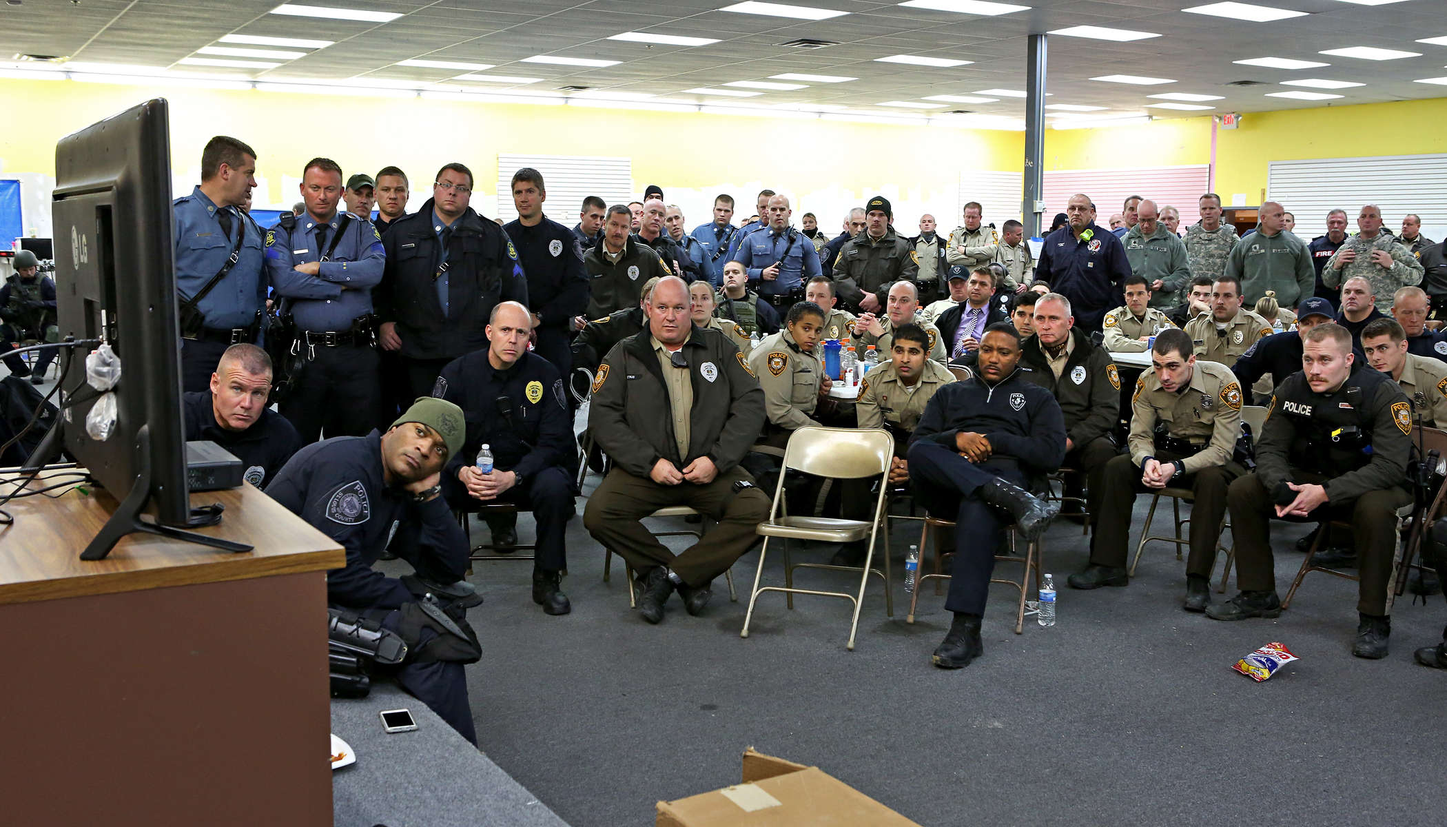 Police officers gather around a television in the unified commend center at the Westfall Plaza shopping center to watch the announcement of the grand jury's decision to not file charges against Darren Wilson in the fatal shooting of Michael Brown on Monday, Nov. 24, 2014. Photo By David Carson, dcarson@post-dispatch.com