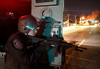 A police officer keeps an eye out for movement along West Florissant Avenue in Ferguson on Tuesday, Nov. 25, 2014.   Smoke from a burning building can be seen rising to the right.Photo By David Carson, dcarson@post-dispatch.com