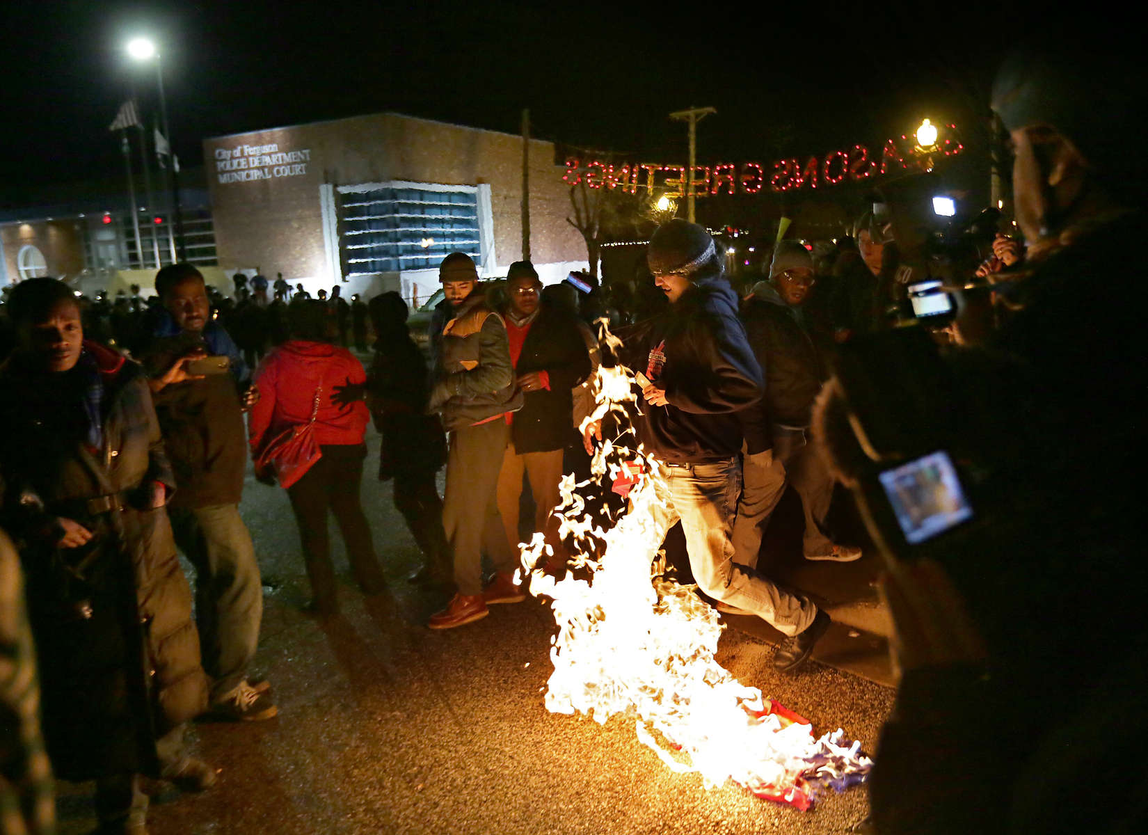 A protester lights a flag on fire outside the Ferguson police department on Saturday, Nov. 29, 2014.  The protester needed to add an accelerant to the flag to get it to burn when they he was unable to get it to ignite with just a lighter.Photo By David Carson, dcarson@post-dispatch.com